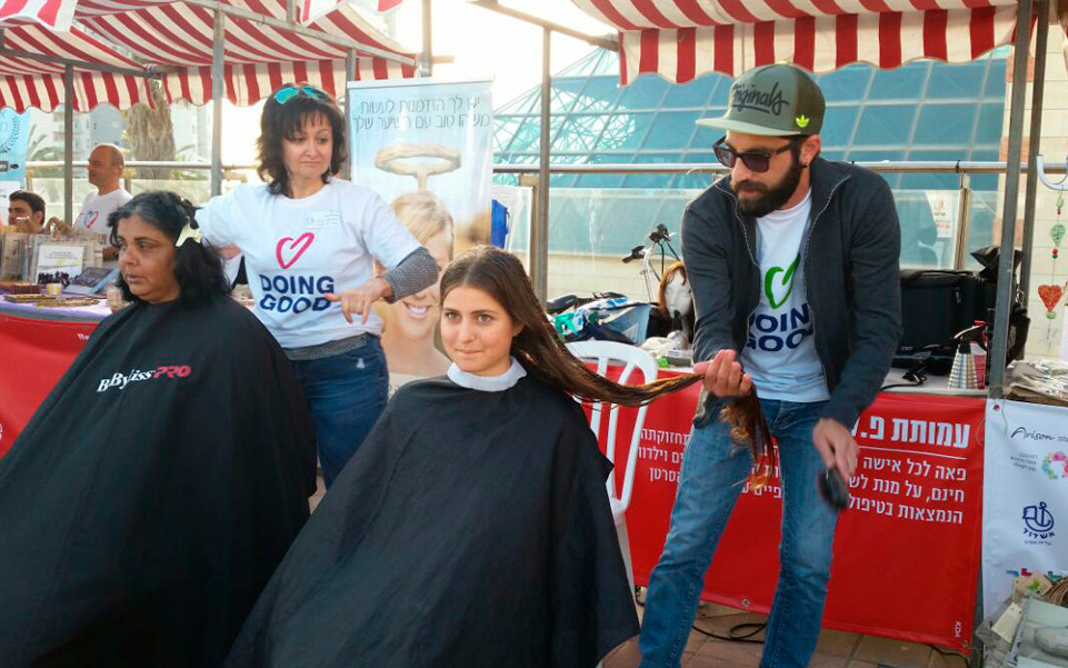 Donating hair at a Good Deeds Day fair